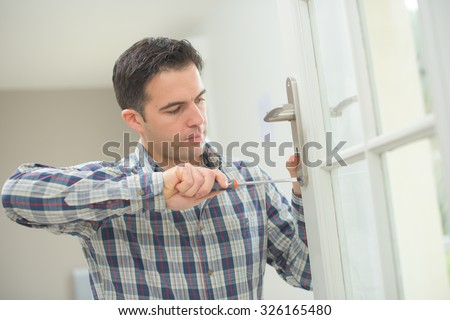 Handyman fitting a new door - stock photo