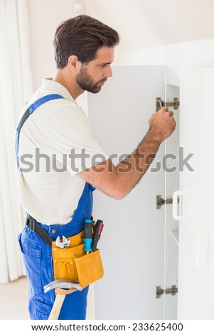 Handyman fixing a wardrobe in a new house