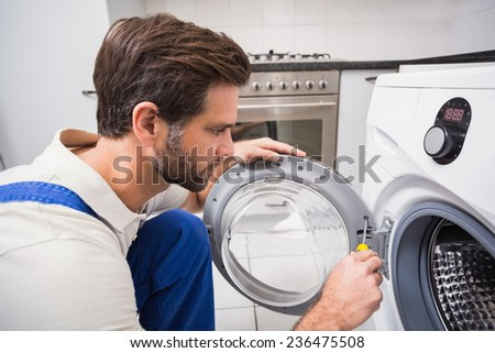Handyman fixing a washing machine in the kitchen - stock photo