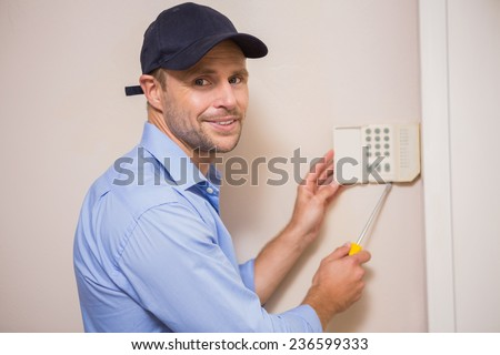 Handyman fixing an alarm system on the wall