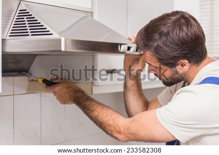 Handyman fixing the oven in the kitchen - stock photo