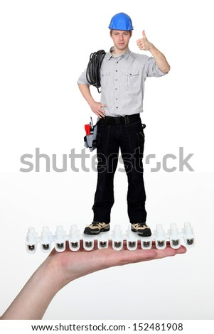 Handyman giving the thumbs-up whilst standing on giant hand - stock photo