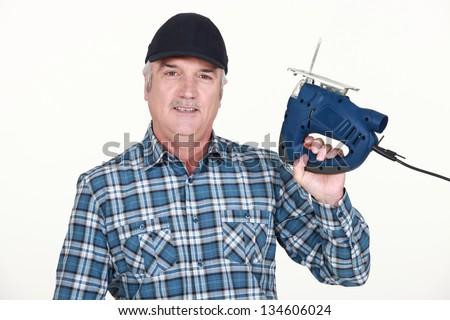 Handyman holding a jigsaw - stock photo