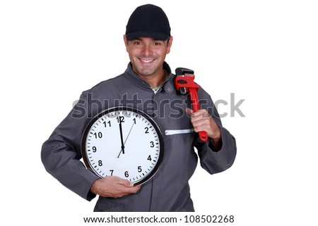 Handyman holding a pipe wrench and a clock - stock photo
