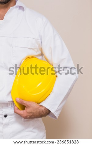 Handyman holding his yellow helmet in a new house