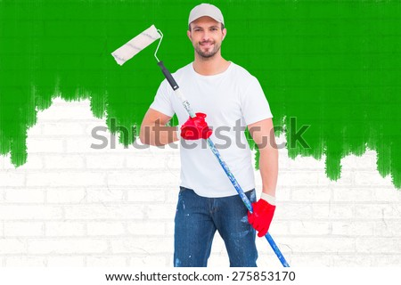 Handyman holding paint roller against white wall