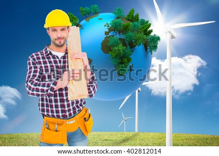 Handyman holding wood planks against digitally generated earth floating in air - stock photo