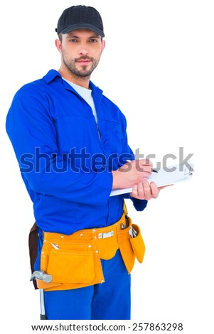 Handyman in blue overall writing on clipboard over white background - stock photo