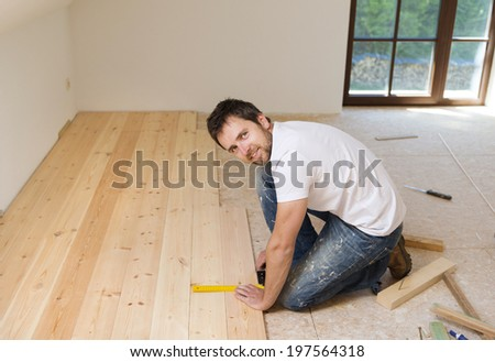 Handyman installing wooden floor in new house