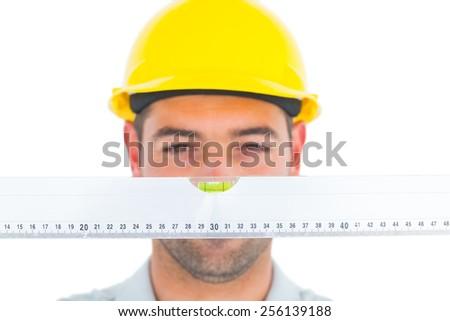 Handyman looking at spirit level over white background - stock photo