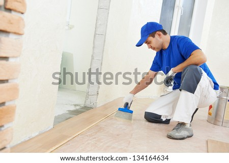 Handyman parquet carpenter worker adding glue on base during indoor wood flooring - stock photo