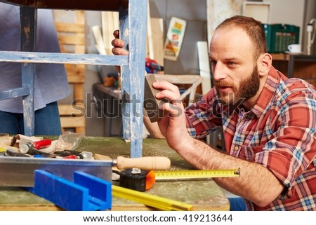 Handyman polishing wooden surface, working in workshop. - stock photo