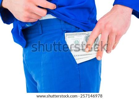 Handyman putting money in his pocket on white background - stock photo