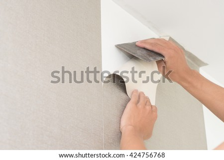 Handyman putting up wallpaper on the wall