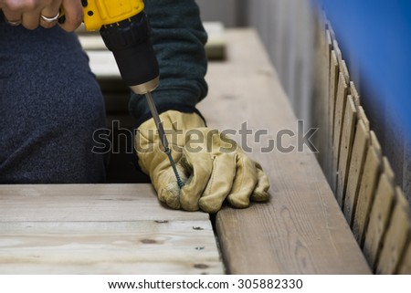 Handyman screwing in deckboards with an electric drill - stock photo