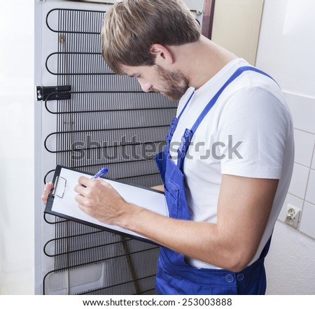 Handyman standing at the fridge and taking notes - stock photo