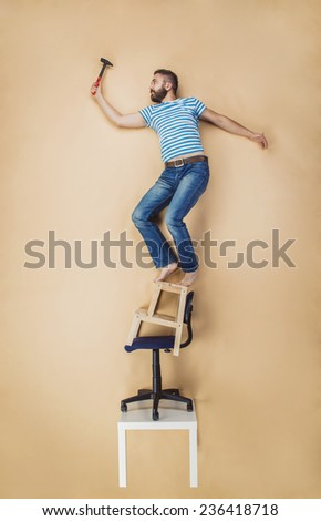 Handyman standing dangerously on a pile of chairs. Studio shot on a beige background. - stock photo