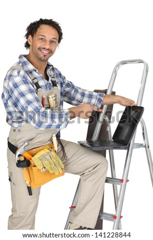 Handyman stood with ladder and pointing at laptop - stock photo
