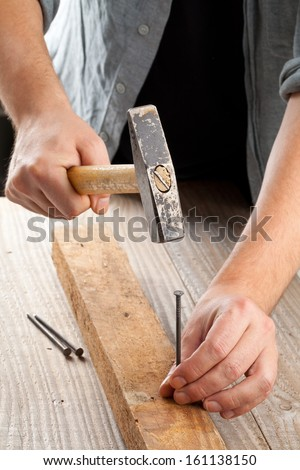 Handyman using hammer and nail - woodworking or do-it-yourself concept