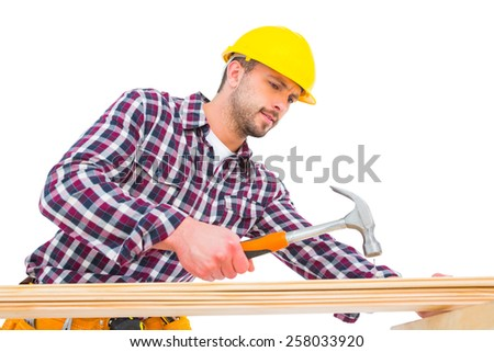 Handyman using hammer on wood on white background - stock photo