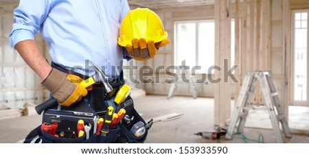 Handyman with a tool belt. House renovation service. - stock photo