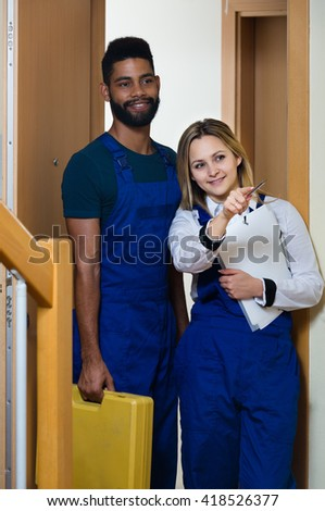 handyman with assistant in uniform at apartment entrance