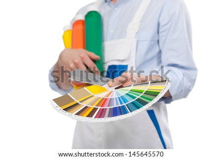 Handyman with paint color cards in the colors of the rainbow held displayed in his hands, cropped view - stock photo