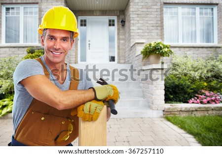 Handyman with wood and hammer. - stock photo