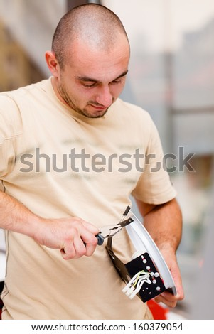 Handyman working with pliers assembling parts. - stock photo