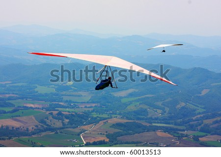 Hang glider flying in the Italian mountains - stock photo