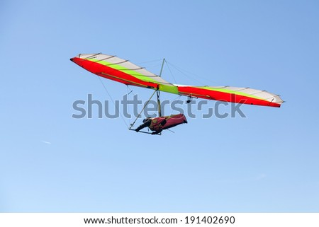 Hang glider flying over a mountain in Greece in a very clear, sunny day - stock photo
