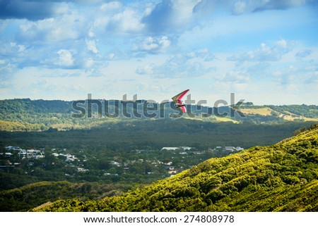Hang glider flying over the valley in Bryon Bay, New South Wales, Australia - stock photo