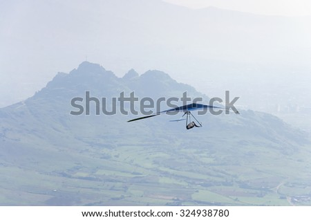 Hang Glider Hang Glider flying in the sky on a bright blue day - stock photo
