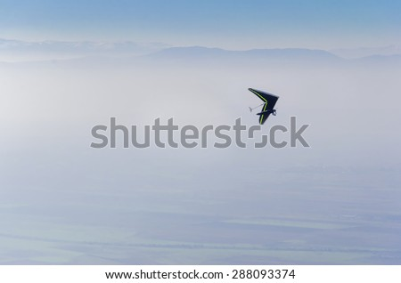 Hang Glider on blue sky. Aerial shot - stock photo