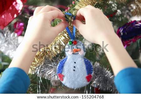 hang handmade xmas decoration on Christmas tree - stock photo