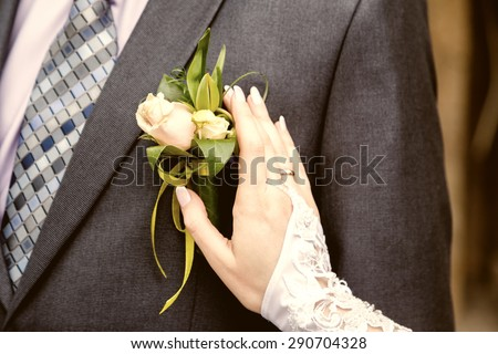 hang of a bride adjusting boutonniere on grooms jacket - stock photo