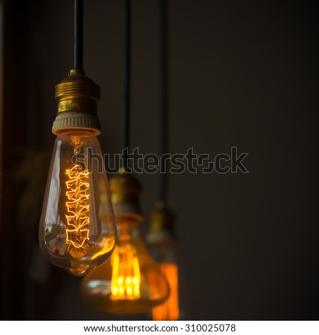 Hanged  decoration light bulbs focus on middle one  in dark room vintage tone vertical