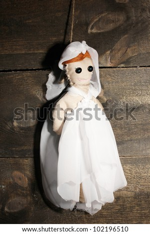 Hanged doll voodoo girl-bride  on wooden background - stock photo