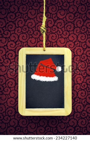Hanged old slate board with Christmas cap chalk drawing - stock photo