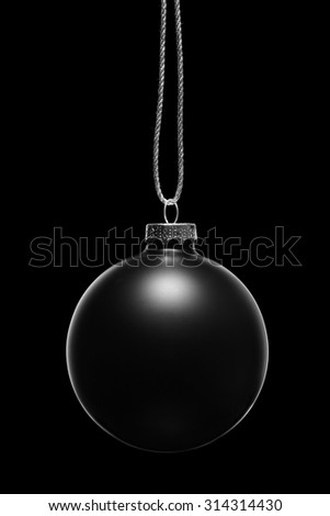 Hanging black Christmas ornament on a black background. Low key. - stock photo