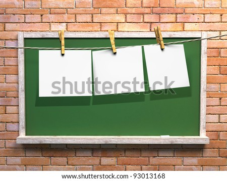 Hanging blank paper on clothesline and green blackboard with wooden frame on brick wall - stock photo