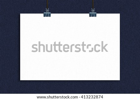 Hanging blank poster on blue jeans texture background.