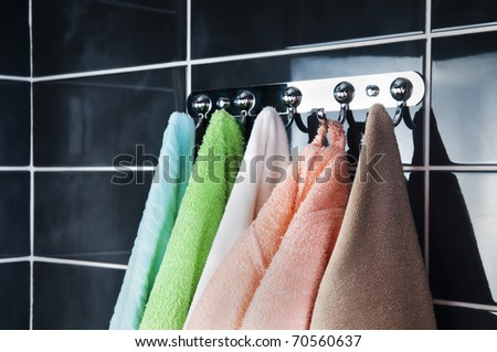hanging bright towels on the background of black tile - stock photo