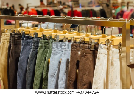 hanging brown, blue, green  pants on hanger in clothing store for sale : beauty and fashion and business concept - stock photo