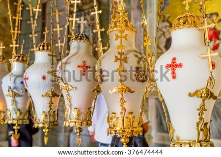 Hanging candle holders at the altar erected over the place of the crucifixion of Jesus Christ in Church of the Holy Sepulchre in Jerusalem, Israel. - stock photo