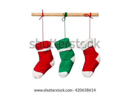 Hanging Christmas socks isolated on white background. Colorful christmas stocking decoration element. red and green knitted sock. Wooden plank and colored ropes - stock photo
