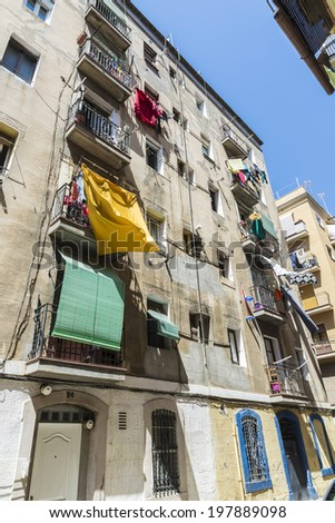 Hanging clothes outside small balconies of old building in the old quarter of Barcelona - stock photo