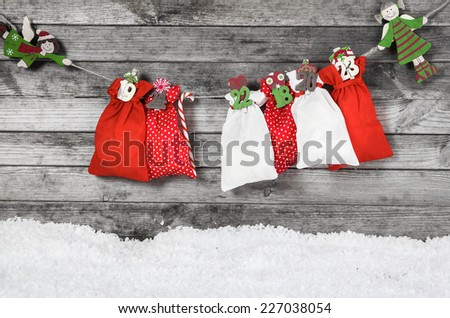 Hanging Colored Christmas Decoration with Santa Sacks, Candy Cane and Kids on Old Gray Wooden Wall. - stock photo
