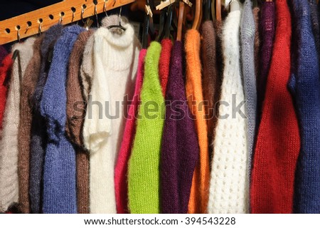 Hanging colorful  knitted colorful clothes - sweaters, dresses, cardigans etc. - stock photo