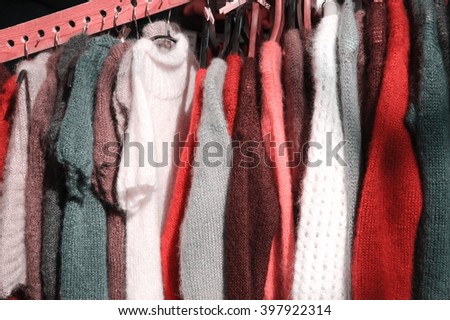 Hanging colorful  knitted colorful clothes - sweaters, dresses, cardigans etc.Toned photo  - stock photo